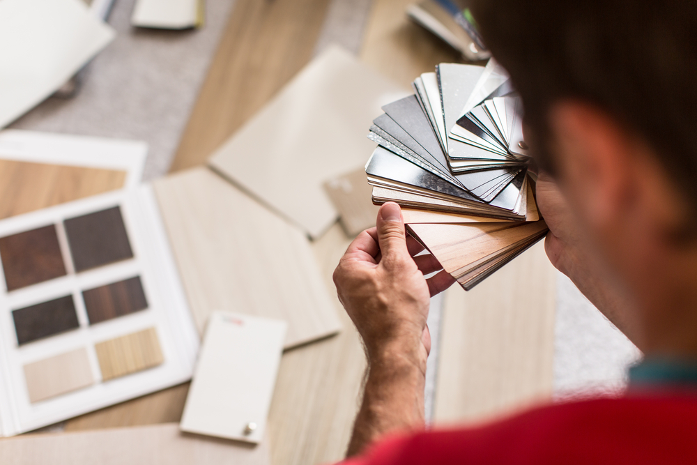 Man looking through different flooring options on a small ring and in booklets